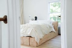 Bed with wooden base in the beautiful farmhouse of interior designer Leanne Ford.
