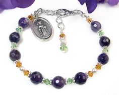 This lovely St. Dymphna chaplet bracelet is handmade from purple amethyst beads, green peridot and topaz crystals, and an Italian-made saints medal.