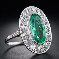 Art Deco Emerald and Diamond Ring - 2.00 carat Emerald to centre surrounded by 14 Diamonds set in Platinum, 1920's.