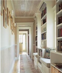 hallway with wood plank ceiling, built in bookshelves, window seat