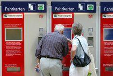 Senioren buchen im Hauptbahnhof in Köln an einem Fahrkartenschalter Tickets bargeldlos