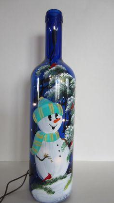 Muñeco de nieve de pie junto a un árbol de invierno Whimiscal con cardenales en una botella azul