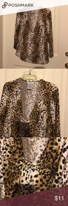 """George Women's Plus Cheetah Print Blouse 18W/20W George Women's Plus size 18W/20W blouse has a Cheetah print. V-neck Blouse is gathered with one piece of the same material stitched to front and inside. Sleeves are 3/4 length. Made in Cambodia of 93% polyester 7% spandex. Armpit to armpit 23"""" across chest. Armpit to hem 14"""". Shoulder to hem about 23"""". George Tops Blouses"""
