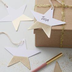 Ces superbes étiquettes en forme d'étoiles sont de couleur blanche et dorée, bi-matière.  Elles seront parfaites en étiquette cadeau ou en marque place pour une fête scintillante ! - decoration white star and gold