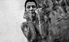 A member of the Street Gang proudly shows off his gang tattoos on 13 May 2011 in San Salvador, El Salvador. Photo by Jan Sochor Lettrage Chicano, Chicano Art Tattoos, Tattoos Skull, Lowrider, Mafia, 18th Street Gang, Outlaw Tattoo, Day Of Dead Tattoo, Chicanas Tattoo