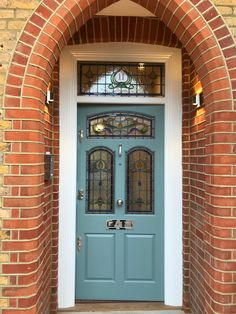 A stunning Bespoke front door in blue-gray finish with beautiful stained glass and polished chrome door furniture. This Edwardian front doors are beautifully framed by amazing brick arch. Front Door Porch, House Front Door, Glass Front Door, House Doors, Garage Doors, Green Front Doors, Painted Front Doors, Front Door Colors, Rustic Exterior
