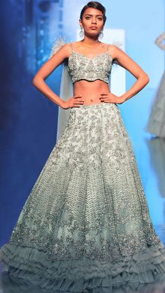The Pearly Feathered Lehenga  The dramatics of this aqua blue lehenga borrows the rhythm of the modern culture and fabulous hand-carved embroideries that transforms this masterpiece into a befitting wardrobe for the bride of today. Suitable for an Indian princess, the lehenga design showcases multi-layered pleats at hem and is heavily embellished in delicate pearls and summer scattered sequins. Put together with a gorgeous strap bustier translates it into a design for present day women!