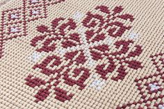 Tappeto realizzato manualmente con la tecnica pibiones punto pieno caratterizzato dal motivo pistoccu. Colore ecru, bianco e amaranto. Misure: 142 X 64 cm. Trat