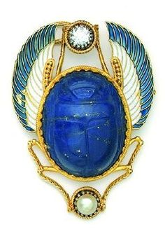 An Egyptian Revival pendant/brooch, by Giacinto Melillo, 19th century. Designed as a scarab of carved lapis lazuli mounted in gold, with wings decorated with blue and white enamel, and legs holding a diamond and a pearl.