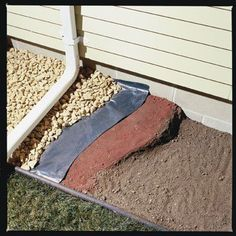 Sloping the soil away from the house. Firmly pack clay soil around the foundation, with at least a 4-in. slope over the first 4 ft. Place 6-mil black plastic over the soil and cover it with landscape rock. Install 4- to 6-ft. gutter extensions to your downspouts to direct water farther away from your foundation.