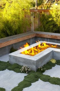 Love the moss between large cement slabs.  Also think the contemporary clean lines like this firepit and bench create a legible effect, while the warm greens and browns of the materials make it cozy.
