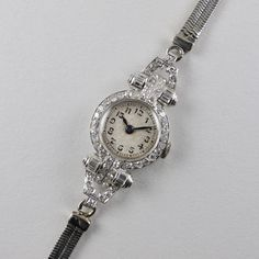 An Art Deco ladys platinum and diamond-set wristwatch with 9ct white gold bracelet  This wristwatch is full of Art Deco style and charm. The platinum case is set with a total of 70 diamonds in a combination of round and baguette cuts. The total diamond weight is well over a carat. The watch is set to a later 9ct white gold snake-form bracelet which carries Birmingham hallmarks for 1956. This watch is accompanied by a heart-shaped retailers presentation case which is covered with b...