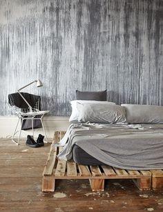 Un sommier en palettes, du linge de lit gris et un mur tout en coulures de peinture… Le style destroy cartonne dans cette chambre !