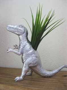 A beautiful silver dinosaur ornament with accented with a faux silk plant. So elegant and classy and are such a unique, fun and elegant addition to