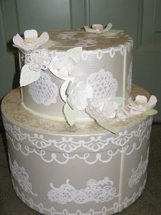 Wedding Cake card box. Made from  old hat boxes. Covered with scrapbook paper.  Cut out flowers, leaves and borders using  a cricut machine.  Could also use other embellishments like ribbon roses, string of pearls, etc.