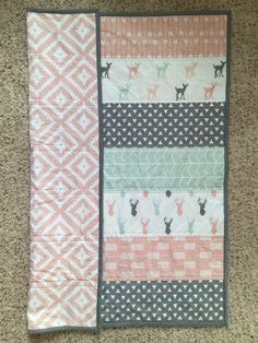 Our Woodland quilt would be a great addition to any Modern baby girls nursery/room. With a combination for modern colors and prints including Deerheads and baby fawn, pink aztec and arrows, mint chevron, and gray triangles.  Both front and back are 100% KONA cotton with a center of cotton batting.Measuring at approximatly 35 x 40 Inches this modern straight lin whole cloth quilt is not only great for snuggling. Its large enough to throw on the ground for a little tummy time but small enough…
