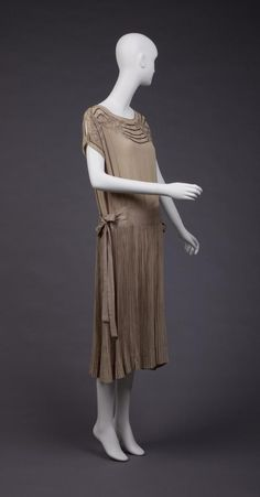 1923, Ecru With Embroidery and Some Beading, Tiny Pleats In Skirts Dropped Waistline, Cap Sleeves, open along shoulderline.  Goldstein Museum