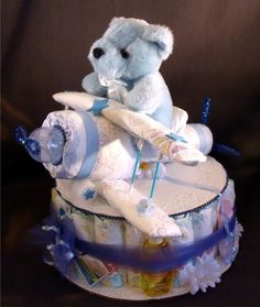 "Bi-plane keepsake made from diapers and baby items ""AIRPLANE"" SHOWER GIFT CENTERPIECE DIAPER CAKE Allow 10 business days for delivery - if you need it sooner please contact me before purchase This is perfect sized for a ""WOW"" baby shower gift, shower table centerpiece, hospital gift, or stopping by to see the new baby at home. It measures approximately 19 inches high and 12 inches wide. It comes to you in a clear gift bag with ribbons and bow - ready to give to the new baby and parents…"