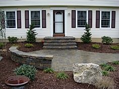 Beautifully-landscaped front yard showing seating wall and landing leading to front steps of home