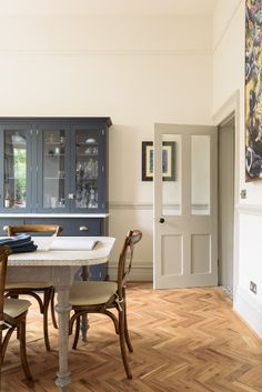 A Pantry Blue dresser with Carrara marble top and parquet flooring are the perfect combination in this deVOL Kitchen