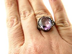 Stunning Amethyst (or glass) untested ring with beautiful unusual setting. Each side has 5 beautiful sparkling marcasites and the band is incredibly