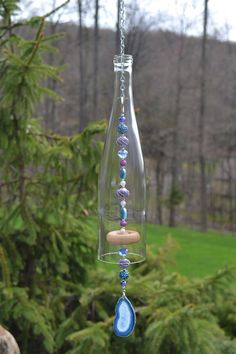 This wind chime is made from a clear wine bottle. I cut the glass myself and sanded the edges. The bottle hangs from silver chain and rings. It has silver, blue, purple and white beads and a wooden knocker that are strung on coated wire. It also has a blue agate slice pendant.  Wind chime measures approximately 27 long including chain and ring for hanging.