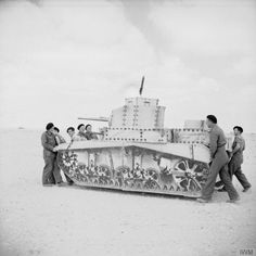 A dummy Stuart tank being carried, April 1942; Up to thirty collapsible dummy tanks such as this could be carried in one truck. Julian Trevelyan, a camouflage officer, describes seeing an entire dummy railhead: 'No living man is there, but dummy men are grubbing in dummy swill-troughs, and dummy lorries are unloading dummy tanks, while a dummy engine puffs dummy smoke into the eyes of the enemy.'