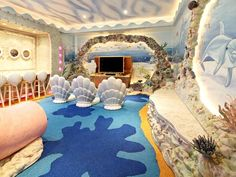Under the Sea  -  No detail was spared in transforming this media playroom into a deep-sea adventure. From the shell-shaped chairs to elaborate mural, this room caters to a kid's dream of living beneath the waves...