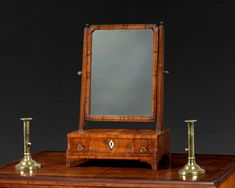 A very pretty George II period walnut dressing mirror, the mirror plate within a moulded crossgrain frame with re-entrant corners, raised on a three drawer stepped base and shaped bracket feet.