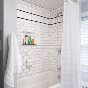 Smoke-colored grout, a row of subways turned on end and bordered with black trim, plus a recessed granite shelf add character and function to the tub alcove.Shower curtain: Target