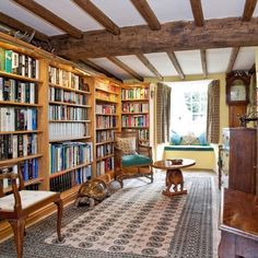 wall to wall plain wood bookshelves & window seat in English country cottage