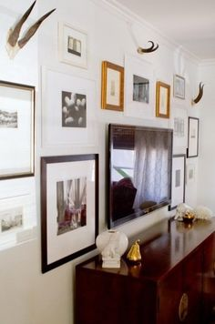 Compose a Gallery Wall Around the TV to make it blend. Symmetry of the surrounding frames make it a more formal arrangement.
