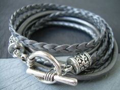 Style# TSB02TW - Get your metallic Gray/Silver on just in time for the Holidays! ... Super stylish and feminine. Wrap it three times around your wrist, toggle up and off you go. This Triple Wrap Leather Bracelet features 3mm round, 3mm braided and 5mm flat braided metallic leather cords. Lead and Nickel Free - Aged Silver Toned Alloy Components, Secure Toggle Closure for Easy on and off. All dyes used in our leather are certified 100% Lead-Free and meet all requirements of the German Goods…