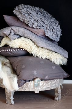 Textile | Decorative pillows in various textured fabrics of grey and purple hues.