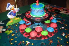Neon blue, green and red single layer cake for birthday boy. Matching cupcakes for guests. Mickey Mouse Clubhouse friends cutouts, stickers and red / black polka dot covered round cake platter