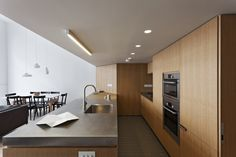 Wooden Cabinets Illuminated by the Lamp and Wooden Dining Table Chandeleir Installed