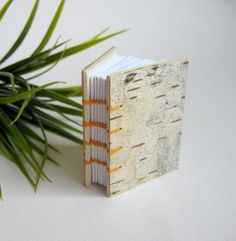 -------About-----------------This is handmade mini journal with 1.7 x 2.2 inches measures,with coptic binding and hard covers which are covered with birch tree bark. This mini book is bind with 100 natural cotton waxed thread and I have used doubled strong craft cardboard for the finish of the mini book.It is small handmade pocket journal for your friends adresses, emails, phone numbers or anything else you need to write while on the road!You know that coptic bound journals do lay flat when…