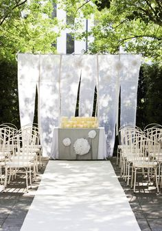 If you're planning on a sunset ceremony but don't want to deal with scattering votives on the ground and don't have access to low-hanging branches, consider setting up rows of candles on a covered table. The candlelight will cast a soft spotlight on the bride and groom as they exchange vows. Source