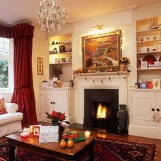 Christmas living room with fireplae, alcove shelving, wood flooring, red curtains and wood coffee table
