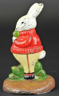 RABBIT IN SWEATER EATING CABBAGE DOORSTOP Albany Foundry, delightful pose  expression of rabbit nibbling on cabbage, dressed in red sweater, pinstripe white pants, very colorful  desirable piece.