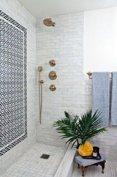 Gorgeous open tile shower with gold/brass fixtures in this modern bathroom
