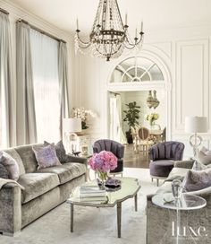This Parisian-inspired living room establishes a serene color palette of white, gray, lavender and mink for the rest of the home. An elegant crystal chandelier hangs over the space.