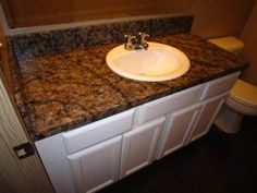 She covered her ugly formica countertop with inexpensive craft paint and a sea sponge. Faux granite without the expensive kit