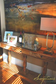 Shallow console table serves as a wine mini bar and highlights beautiful art in a tight space
