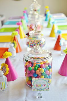 Rainbow Birthday Table: The table is set! A simple white fabric covered the lunch table, adorned with bright party hats and matching plates in every color. Source: Belva June