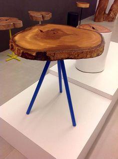 Detalhes de mesas de apoio com tampo de tronco de madeira.