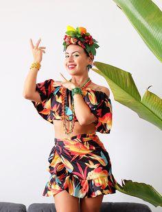 Carol Burgo veste fantasia de Carmen Miranda estampada, para curtir o Carnaval de rua. Tiara de frutas, blusa ciganinha e saia com babados.