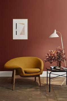 Ajouter un fauteuil scandinave confortable associé à une petite table basse sur laquelle on pose des livres et bouquet de fleurs séchées