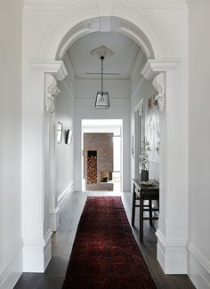 This victorian hallway has ornate carved details, a narrow console table, deep red runner rug, simple hanging light fixture and a modern brick fireplace at the end.