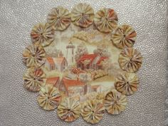 This is a beautiful doily featuring the colors of autumn highlighting a lighthouse in the background of quaint cottages. It is rimmed with handsewn yo